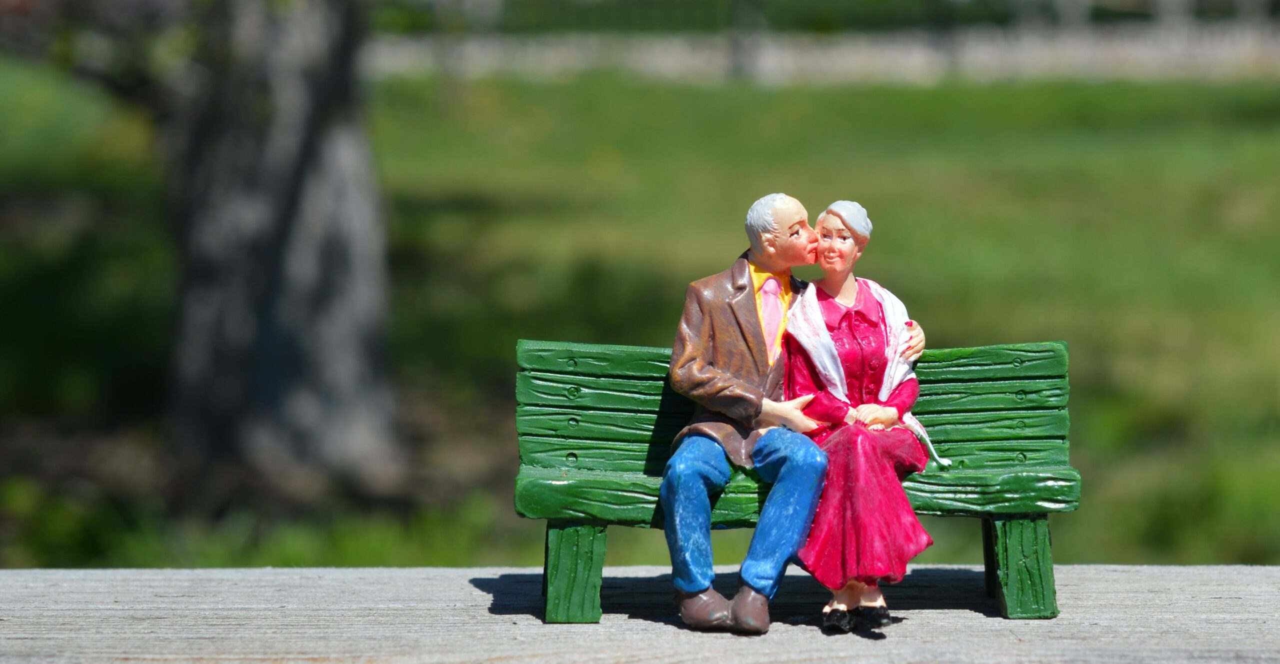 new Medicare card | old couple on bench | HealthCare.com