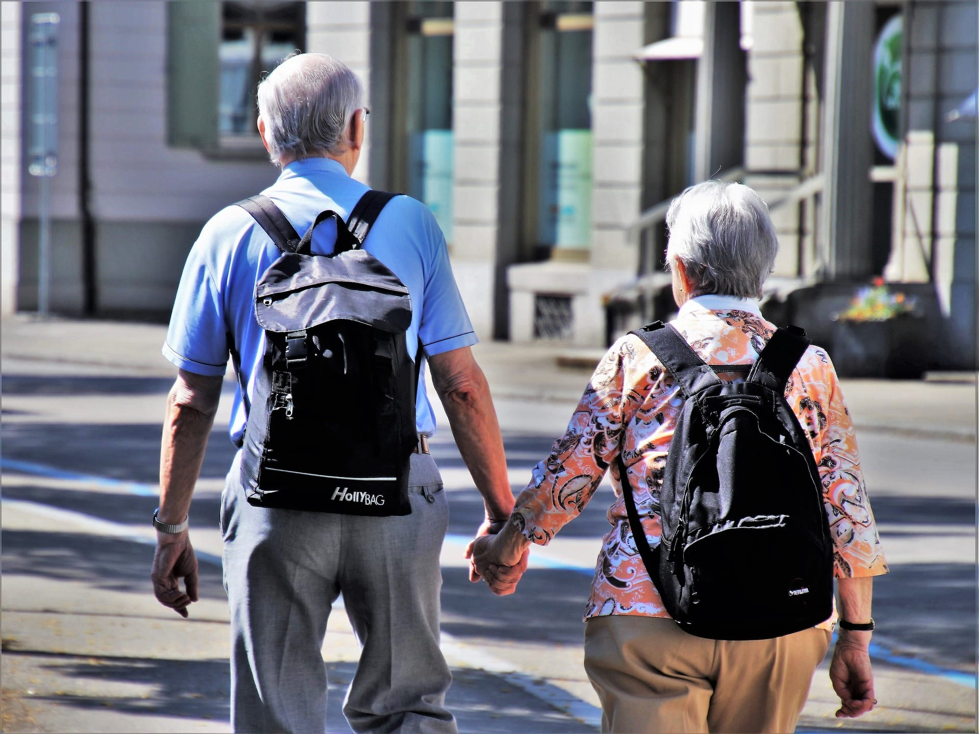 two seniors with backpacks holding hands during travel | Medicare Annual Wellness Visit