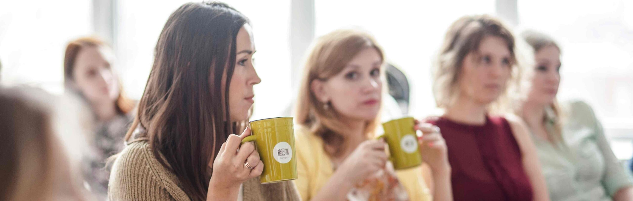 women drinking coffee in audience | health insurance premiums